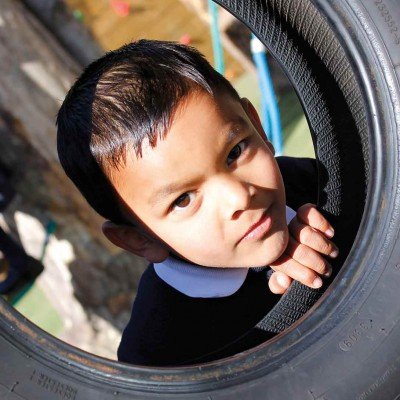 Child looking through tyre